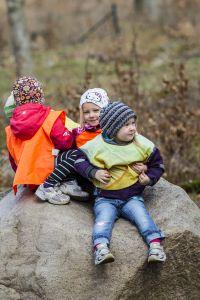 Barn som sitter utomhus på en sten. Foto.