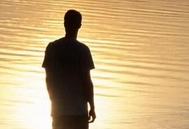 Siluett av en man som står vid en sjö. Foto.