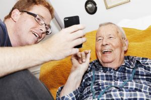 Skrattande äldre man tillsammans med skrattande yngre man. Foto.