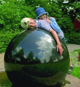 Barn som hänger på en stor stelkula. Foto.