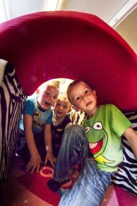 Barn som leker i en tunnel inomhus. Foto.