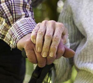 Två äldre personer som håller varandras händer. Foto.