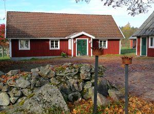 Rött trähus med vita knutar. Foto.