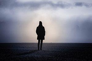 Siluett av gående kvinna. Foto.