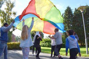 Barn och vuxna som leker med färgglad fallskärm.