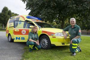 Två ambulanspersonal sitter framför en ambulans. Foto.