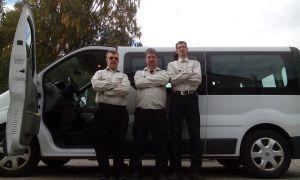 Tre personer står framför en minibuss. Foto.