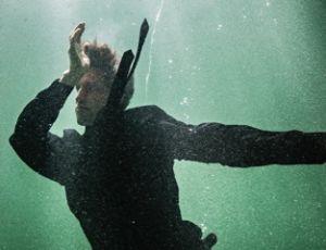 Man i kläder under vatten