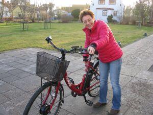 Unna Stenram, bibliotekarie i Broby visar upp elcykeln, som nu kan lånas.