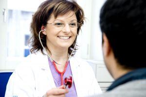 Leende kvinnlig läkare med patient. Foto.