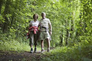 Ett par vandrar hand i hand på en gångväg i naturen.