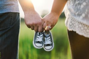 Ett par håller varandra i hand samtidigt som de håller ett par barnskor. Foto.