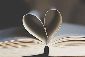 Uppfälld bok med blad format som ett hjärta. Foto.
