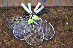 Tennisracket som ligger på marken.