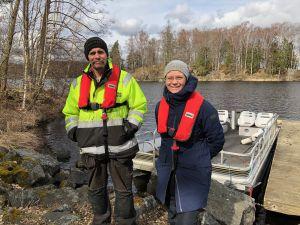 Två personer står iklädda flytvästar på en ö i sjön Immeln.
